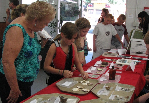Visitors examine artifacts from the 2013 dig